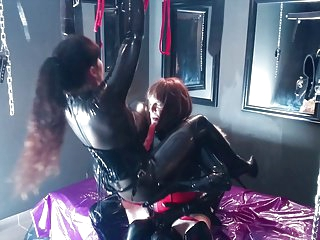Latex Slut gets spit roasted by two beautiful dommes!