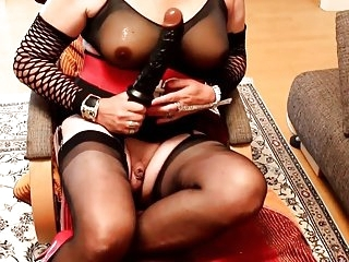 Mature Transvestite playing with a fist dildo